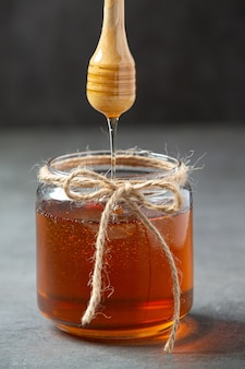 어두운 표면에 나무 꿀 디퍼와 함께 맛있는 꿀