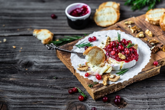 Delicious hot baked camembert with fresh rosemary, cranberry sauce and baguette bread on wooden table.