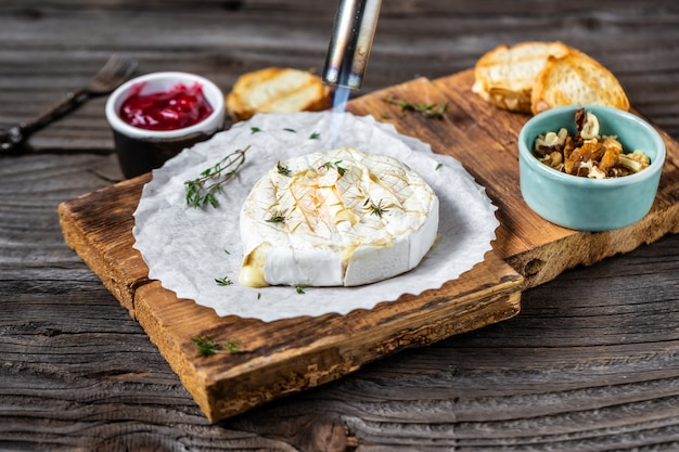 Delicious hot baked camembert with fresh thyme, cranberry sauce and baguette bread on wooden table.