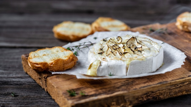 Delicious hot baked camembert with thyme and baguette bread on wooden table.