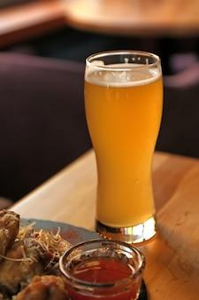 おいしいホットバーベキューウィングとビールをテーブルでお召し上がりいただけます