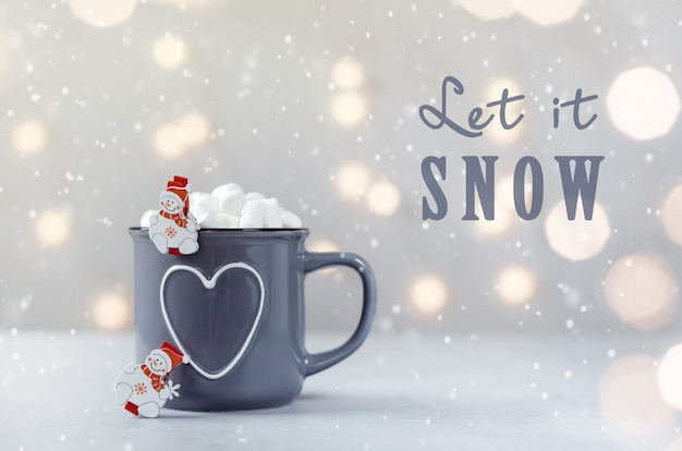 Delicious hot chocolate with marshmallow and litle snowmans on grey stone background