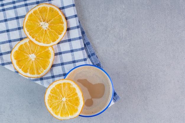 맛있는 뜨거운 커피와 돌 테이블에 슬라이스 오렌지.