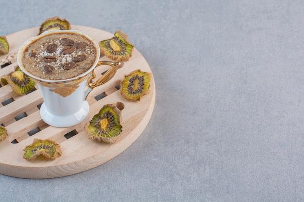 Вкусный горячий кофе в белой чашке с сушеным киви.