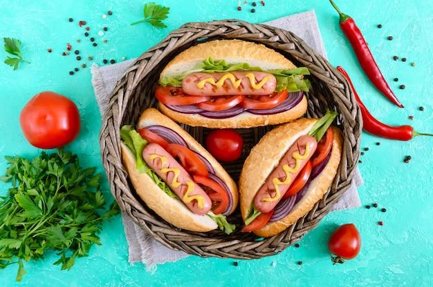 Вкусный хот-дог в корзине. жареная колбаса с помидорами, красным луком, листьями салата, горчицей в хрустящей буханке. уличная забегаловка. быстрое питание. вид сверху