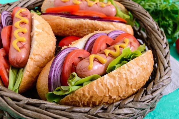 Вкусный хот-дог в корзине. жареная колбаса с помидорами, красным луком, листьями салата, горчицей в хрустящей буханке. уличная забегаловка. быстрое питание.