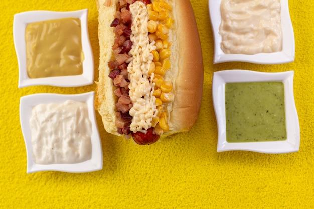 カラフルなまたは木製の背景に食材とおいしいホットドッグ