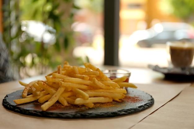 테이블에 제공되는 빨간 소스와 함께 맛있는 뜨거운 감자 튀김