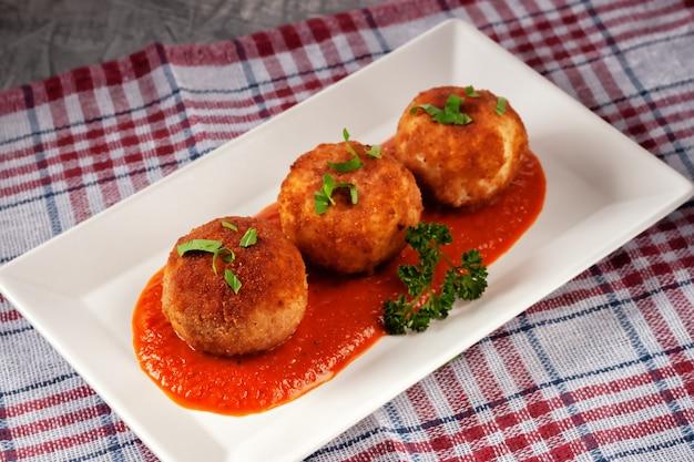 맛있는 뜨거운 이탈리아 아란 치니-오래된 나무 테이블에 접시에 토마토 소스에 치즈로 채워진 주먹밥