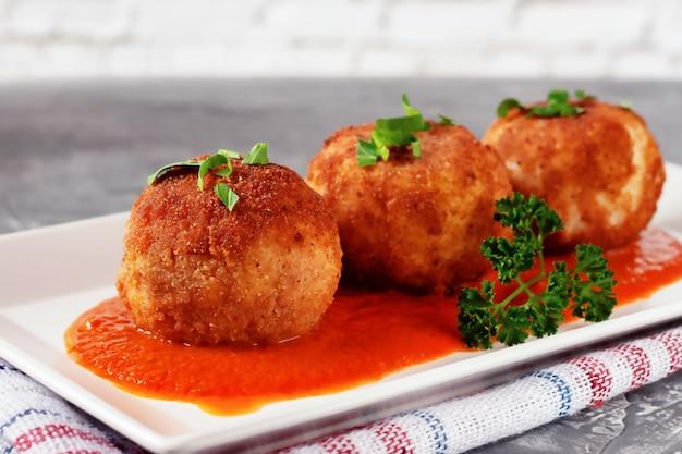 おいしいホットイタリアンアランチーニ-古い木製のテーブルのプレートに、トマトソースにチーズを詰めたおにぎり