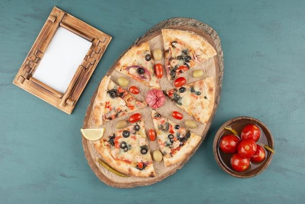 Вкусная горячая пицца, миска маринованных помидоров и фоторамка на синем столе.