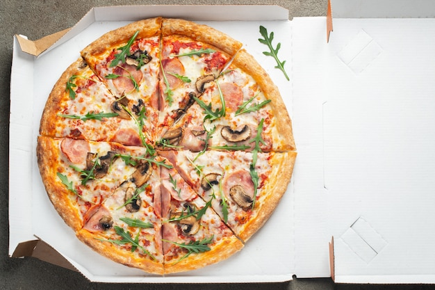 Delicious hot pizza in a box with ham.