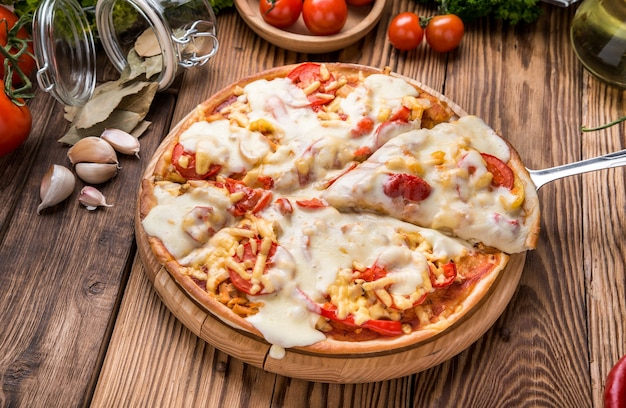 Delicious hot pizza piece on wooden spoon with melting cheese