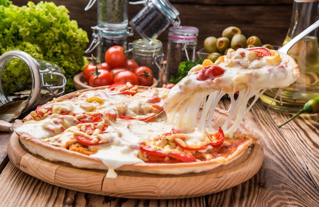 Delicious hot pizza piece on wooden tray with melting cheese