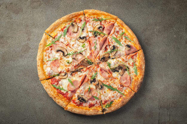 Delicious hot pizza with ham and champignons.