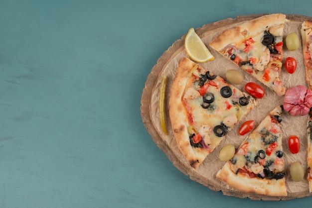Вкусная горячая пицца с оливками и помидорами на синей поверхности.