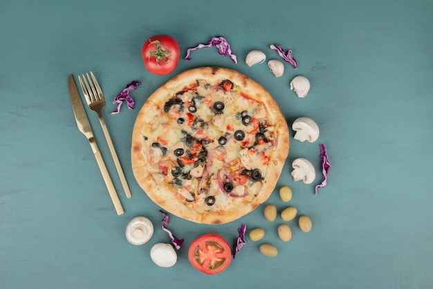 Вкусная горячая пицца с оливками, грибами и помидорами на синей поверхности.