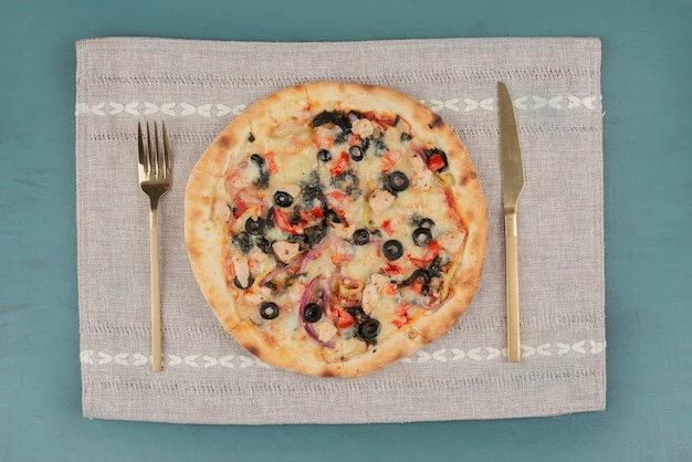 Deliziosa pizza calda con olive e pomodori sul tavolo blu con posate d'oro.
