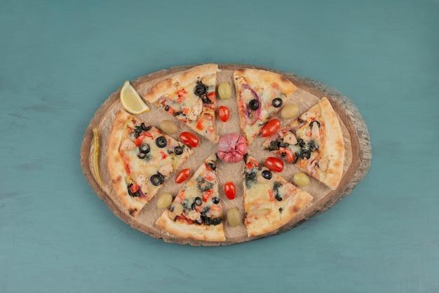 Deliziosa pizza calda con olive e pomodori sul tavolo blu.