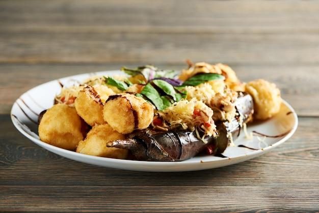 Вкусное горячее ресторанное блюдо, в которое входит золотистый картофель, обжаренный с сыром, и сочные овощи гриль. вкусная закуска, украшенная свежими листьями мяты и соусом.
