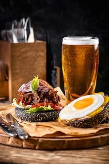 白い木のテーブルのまな板に唐辛子とビールのグラスとおいしいホットスパイシーな黒のハンバーガー。