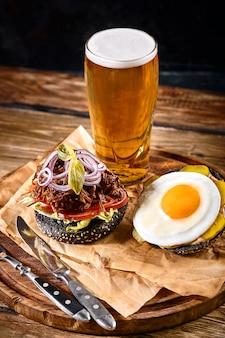 白い木のテーブルのまな板に唐辛子とビールのガラスとおいしいホットスパイシーな黒のハンバーガー