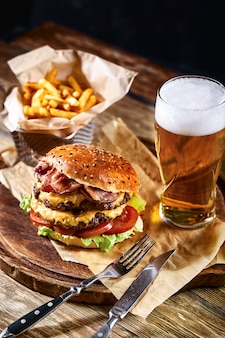 Delicious hot spicy black burger with chili pepper and glass of beer on cutting board on white wood table