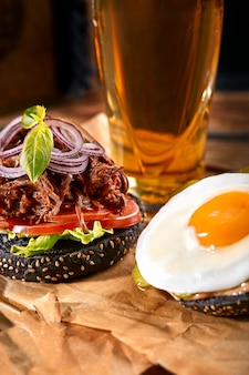 Delicious hot spicy black burger with chili pepper and glass of beer