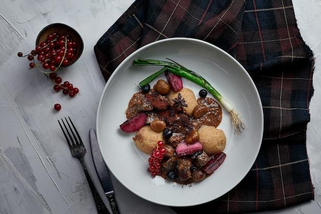レストランの背景にベリー、野菜、ソースが入ったおいしいフムス料理。レストランのフムス料理。