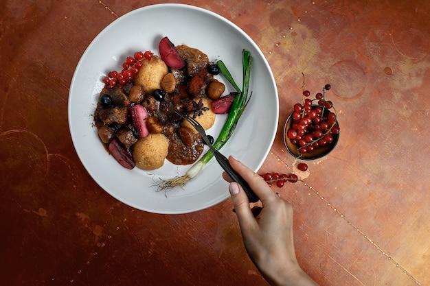 레스토랑 배경에서 딸기, 채소, 소스를 곁들인 맛있는 후무스 요리. 레스토랑용 후무스 요리.