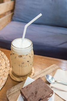 Delicious ice coffee and chocolate brownie serve on wooden tray with tissue paper with spoon Premium Photo