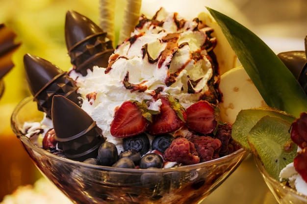 Delicious  ice cream with fruits, chocolate, nuts in glass bowl. close up