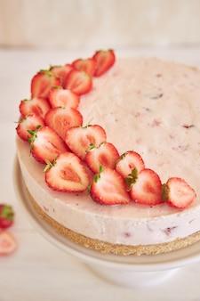 Deliziosa torta allo yogurt gelato con fondo di biscotti e fragole