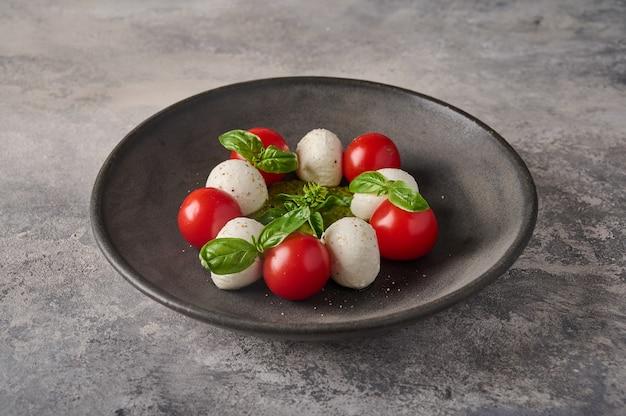 完熟トマトのフレッシュバジルとモッツァレラチーズのブラックプレートを添えた美味しいイタリアンカプレーゼサラダ