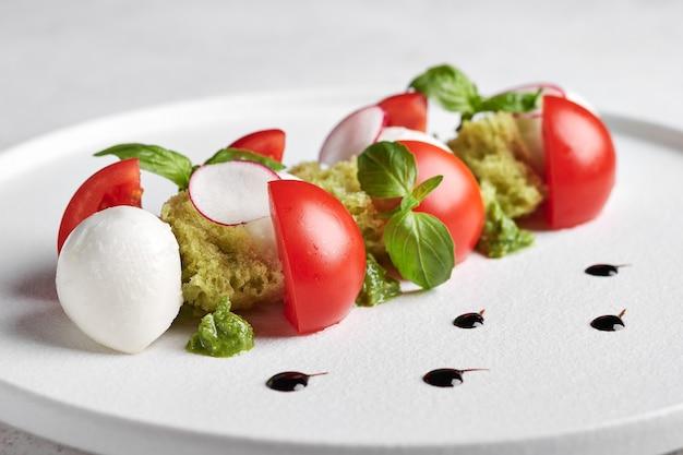 Вкусный итальянский салат капрезе со спелыми помидорами, свежим садовым базиликом и сыром моцарелла