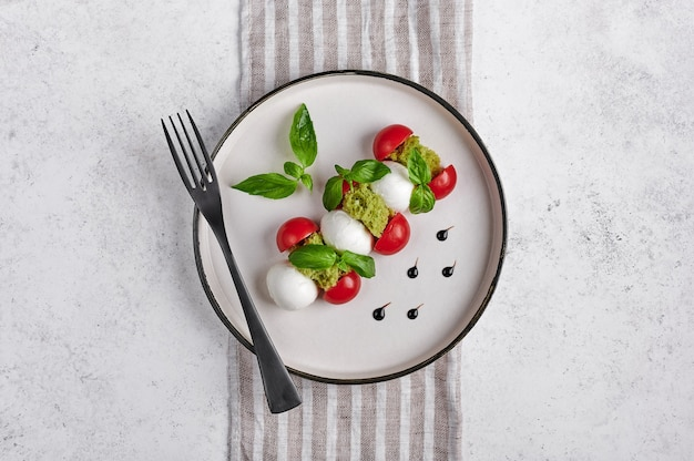 Delicious italian caprese salad with ripe tomatoes, fresh garden basil and mozzarella cheese with fork on linen napkin