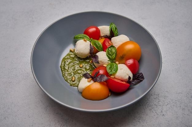 完熟トマト、松の実、バジル、モッツァレラチーズのグレーの美味しいイタリアンカプレーゼサラダ