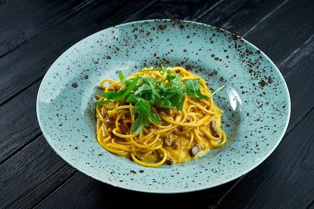 Вкусная итальянская паста карбонара с беконом и сырым желтком, пармезаном и рукколой.