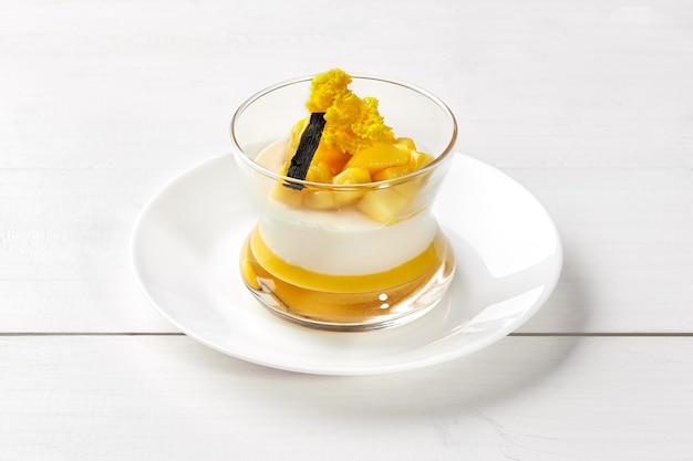 マンゴーピューレの層とバニラスティックを添えた新鮮な熟した果物の断片が白い木製の背景にガラスで提供されるおいしいイタリアのクリーミーなパンナコッタ。人気のデザートコンセプト