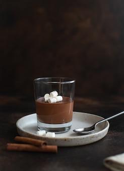 Delicious italian dessert panna cotta with dark chocolate, decorated with marshmallows dark surface