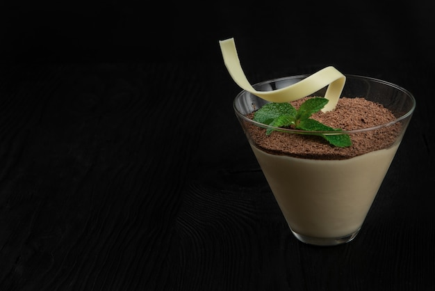 Delicious italian dessert tiramisu on a black wooden background decorated with mint leaf with copy s...