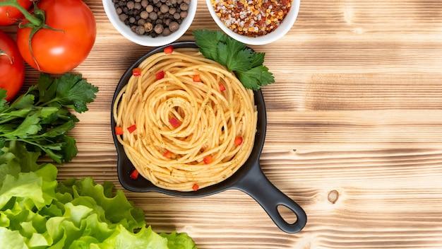調味料とハーブの上面図が付いたおいしいイタリアンパスタ