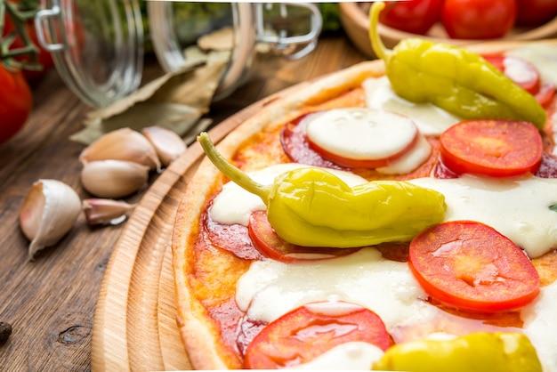 木製の机の上のレストランでおいしいイタリアンピザ