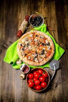 生地に美味しいイタリアンピザ。木製のテーブルの上。上面図