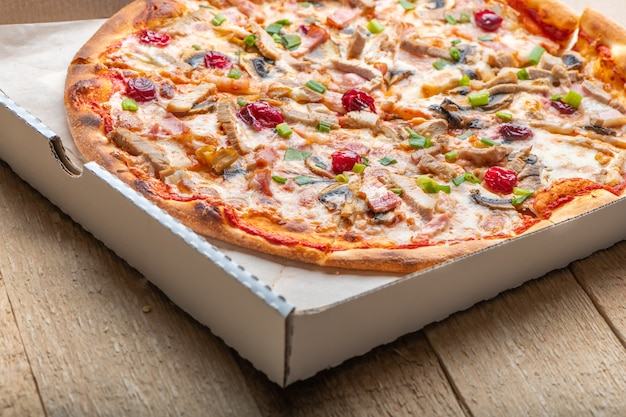 Delicious italian pizza with cheese mozzarella , tomatoes, bacon, mushrooms and green onion