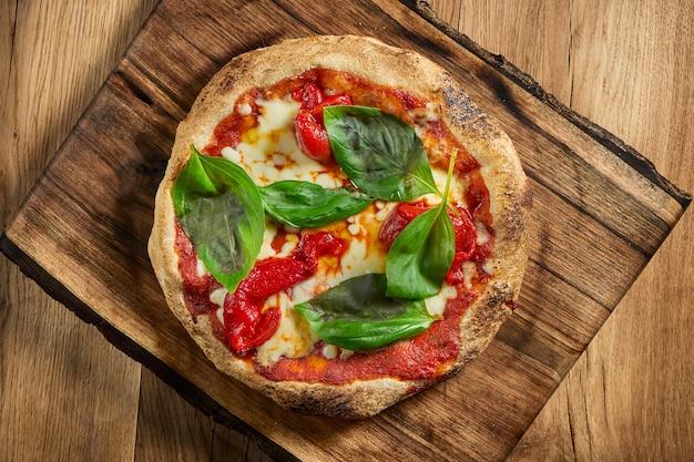 カリカリのサイドとトマト、スモークピーマン、ほうれん草を詰めたおいしいイタリアンピザ。木製のテーブルの上のピザマルゲリータ