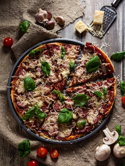 きのこ入りのおいしいイタリアンピザを木製のテーブルでお召し上がりいただけます