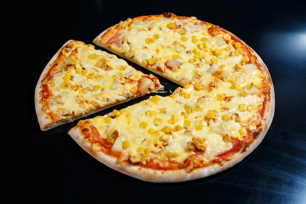 Delicious italian pizza with raw meat, tomatoes and olive oil on a dark concrete table. top view with copy space.