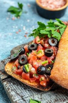 グリルしたバゲットにオリーブ、野菜、ハーブ、オイルを添えたおいしいイタリアントマトのブルスケッタチャバタ。垂直方向の画像。上面図。