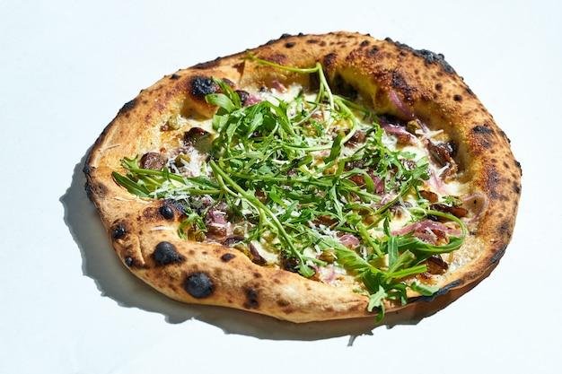 Вкусная итальянская пицца на дровах со сливочным соусом, вешенками, каперсами, рукколой и трюфелем на серой поверхности. жесткий свет.